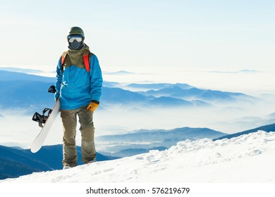 Close up shot of a snowboarder in helmet standing at the top of a mountain with his snowboard in hand