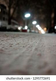 Close up shot of snowy street with tire marks, cars and street lights in background out of focus