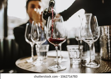 A close up shot of a sommelier pouring red wine into a wine glass. Selective focus point on the wine drops and the glasses. Other glasses in the background are out of focus. Wine training and tasting
