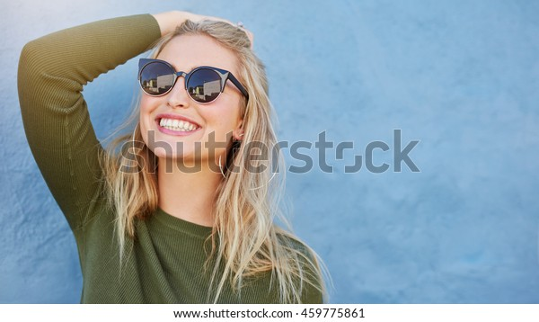 Close up shot of stylish young woman in sunglasses smiling against blue background. Beautiful female model with copy space.