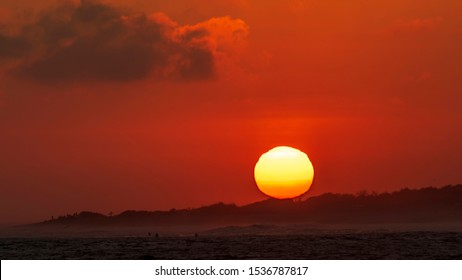 Close up shot of the sunset sunball as it dips behind the beach head near the surf spot Lower Trestles in San Clemente, Southern California.
