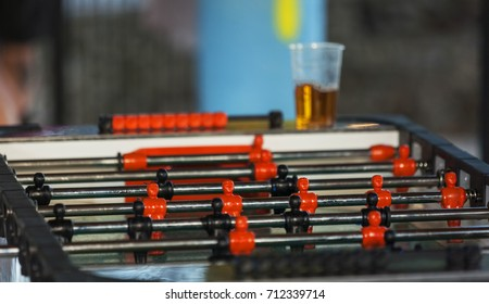 Close up shot of table soccer, black and red players and beer