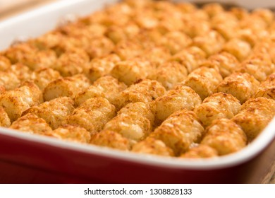 A close up shot of tater tot hot dish in a red baking pan.