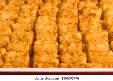 Close up shot of tater tot hot dish shot with a shallow depth of field in a red baking pan.