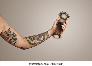 eb8dd7584a176 A close up shot of a tattooed arm and hand holding a light gray aeropress (