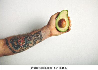 Close up shot of a tattooed man's arm with a half of ripe fresh avocado isolated on white
