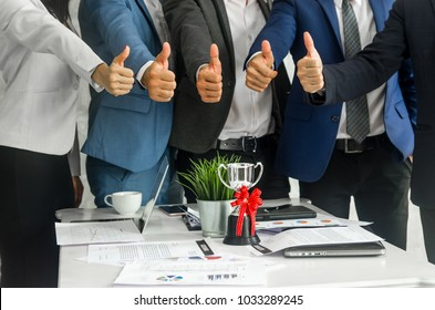 Close up shot  team of businesspeople give thumbs up over the trophy in meeting with notebook and paper charts. Good teamwork , Goal setting and work commitment concept.
