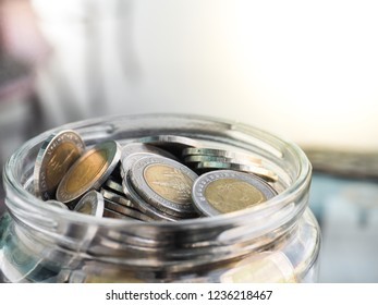 Close up shot of Thai Baht 10 baht coins in the gass jar with text space on the top right