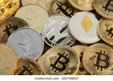 Close up shot of three main cryptocurrencies; bitcoin, ethereum and litecoin on gold surface