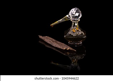 Close Up Shot Of Traditional Luxury Arabic Oud Oil Perfume In A Beautiful Handmade Clear Crystal Glass Jar Bottle & Glass Dropper & Agar wood Isolated On Black Background Antique Style, Text Space
