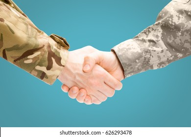 Close up shot of two military men shaking hands on light blue background