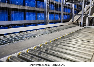 Close up shot of two roller conveyors in an automated warehouse with a ramp and piles of blue plastic boxes in the background. Photo taken in a big warehouse in Germany. Focus on the conveyor rolls.