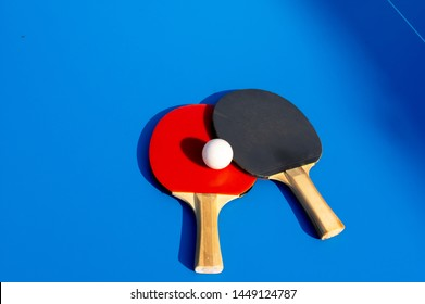 close up shot of two table tennis paddles with a ball on blue table