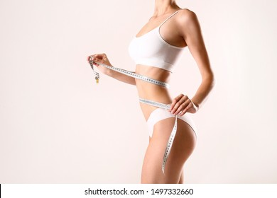 Close up shot of unrecognizable fit woman in lingerie measuring her waist with a tape isolated on white background. Torso of slim attractive female with flat belly in white underwear. Copy space.