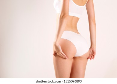 Close up shot of unrecognizable fit woman in lingerie isolated on white background. Back view of slim attractive female with bubble shaped buttocks in white underwear. Copy space for text.