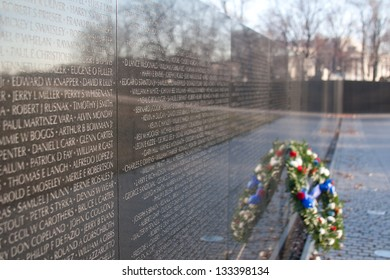 Close shot of the Vietnam Memorial, with a few names clearly seen, and a wreath sitting near by.