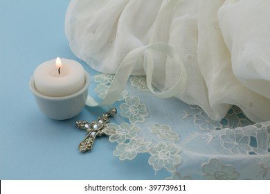 Close up shot of vintage baptism dress on blue background with cross and candle