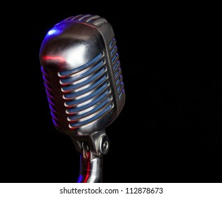 Close up shot of a vintage microphone with reflection of colored lights with a black background