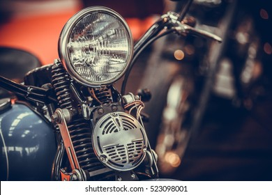 Close up shot of a vintage motorcycle headlight and horn.