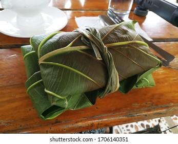 Close shot of vunong, a traditional Ivatan meal wrapped in big kabaya leaves and served as two-leaf packets tied together, one contains the turmeric rice and the other the four viands.