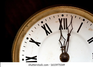 Close up shot of a wall clock with roman numerals.