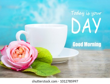 close up shot, white coffee cup and beautiful pink rose on blue and  old rustic wood background, morning breakfast concept with Good morning today is your day quotes