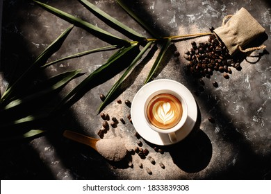 Close up shot of white coffee cup, hot cappuccino with heart-shaped latte art and flowers, food and drink concept.