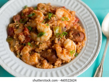 Close up shot of a white ribbed bowl filled with shrimp and andouille sausage Jambalaya. Scallion garnish.
