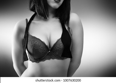 close up shot of woman breasts in underwear with a untided bow tie around her neck
