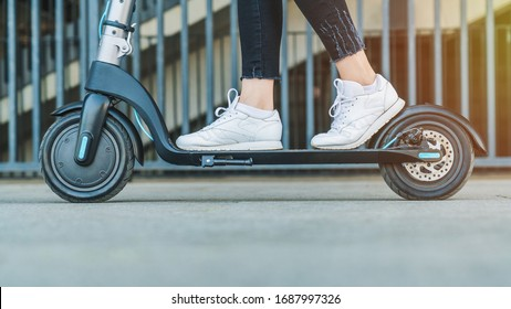 Close up shot of woman having fun and rides electric scooter at the street