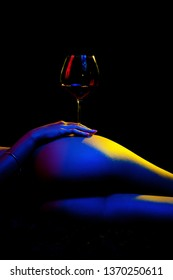 Close up shot of a woman laying on her side holding a glass of red wine on top of her butt and hip. There is a black background behind her and her body is covered in blue, red and yellow studio lights