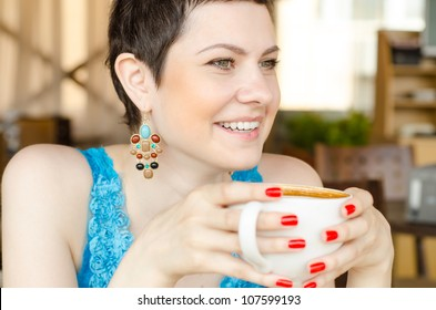 A close up shot of a woman looking forward, as she holds a mug u