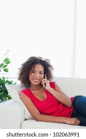 A close up shot of a woman making a call on the phone while smiling.