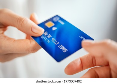 Close up shot of a woman passing a payment credit card to the seller. Woman hand giving credit card to cashier. Detail of girl giving bank creditcard for payment to waitress.