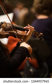 Close up shot of a woman performing on a violin during a concert.