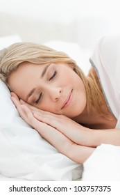 A close up shot of a woman resting in bed with her hands pressed on the pillow beside her head.