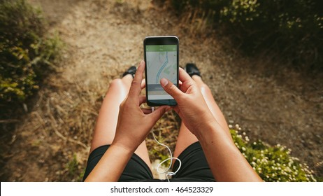 Close up shot of woman runner using a fitness app on her smartphone. Female checking the summary of her run on mobile phone. POV shot with focus on cellphone in hands.