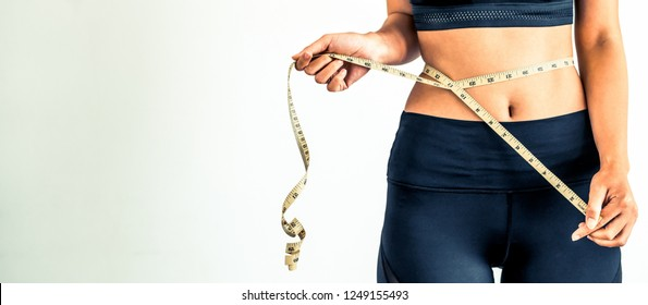 Close up shot of woman with slim body measuring her waistline and torso. Healthy nutrition and weight losing concept.