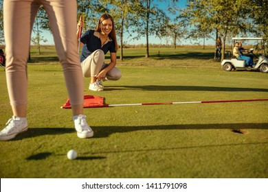 Close up shot of a woman taking a putt on a golf green, while the other woman is watching