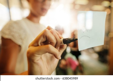 Close up shot of woman writing on sticky note during office meeting. Female executive discussing business ideas with colleagues sitting in background.
