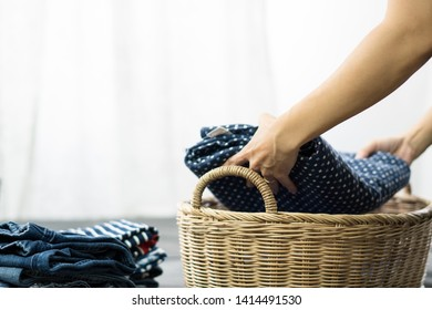Close up shot of woman's hands doing the laundry work. She putting clean folded cloths and towels into a laundry basket. Woman, Wife, Mom daily routine housework concept.