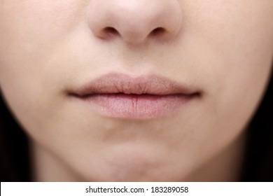 close up shot of a woman's mouth with very little make up on