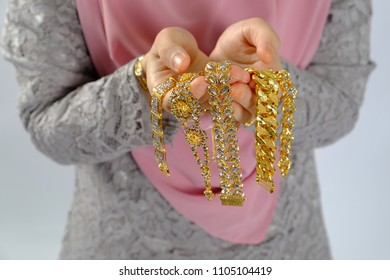 Close up shot of women hand holding gold expensiv jewelry