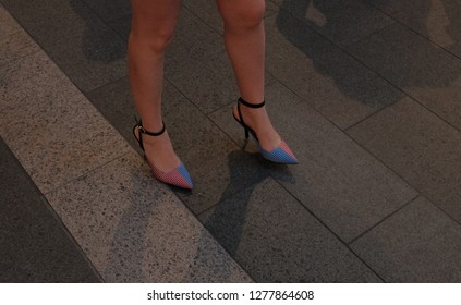 Close up shot of women legs with colorful shoes.