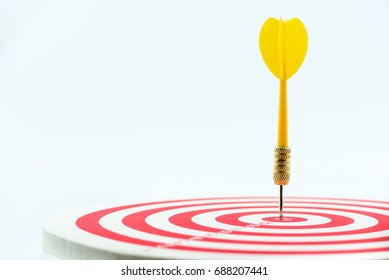 Close up shot of yellow dart or missile hit in the center / middle of a target marked with score numbers. Dart and target is used in sport or in business metaphor i.e target audience, target area, etc