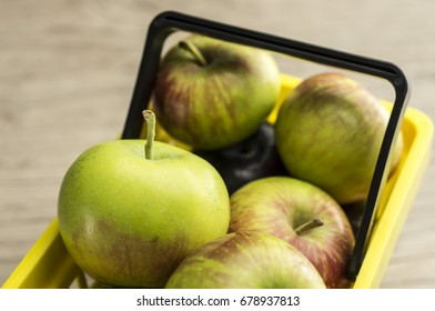 Close up shot of a yellow supermarket basket filled with apples
