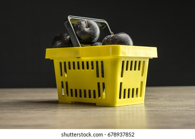 Close up shot of a yellow supermarket basket filled with plums