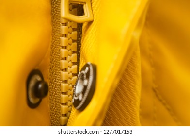 Close up shot of a yellow zipper on a yellow jacket.