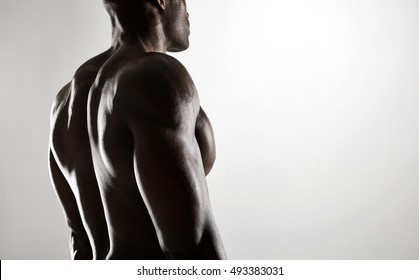 Close up shot of young african man with muscular body against grey background. Shirtless male model with muscular back.