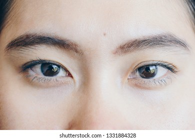 Close up shot of young Asian woman face, open her eyes and looking to the camera.
